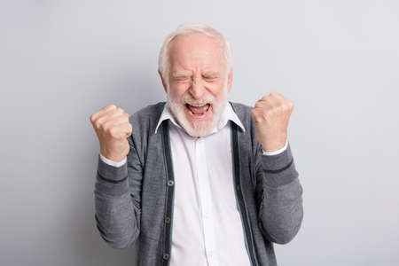 Portrait of old white hair hooray funny man hands fists closed eyes wear dark sweater isolated on grey background
