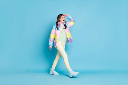 Photo portrait full body view of walking girl looking in distance with hand on forehead isolated on pastel blue colored background