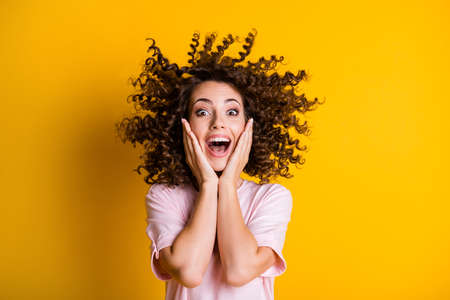 Photo portrait of amazed curly girl laughing touching cheeks with both hands opened mouth isolated on bright yellow color background Фото со стока