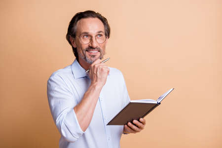 Photo of minded man hold diary pen look empty space wear eyeglasses shirt isolated beige color background