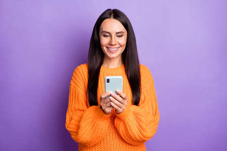 Portrait of charming positive girl hold phone typing comment wear pullover isolated on purple color background Stock Photo