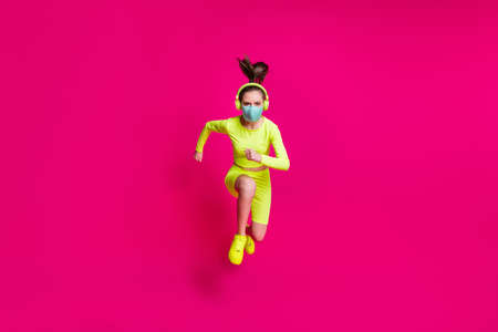Full length body size photo of female runner jumping high running fast wearing covid-19 mask isolated on vibrant fuchsia color background