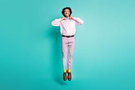 Full body photo of happy guy jump touch his bow dressed formal outfit yellow socks isolated on turquoise color background