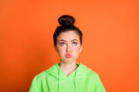 Photo portrait of pouting girl looking up isolated on vivid orange colored background