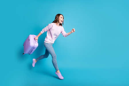 Full size profile side photo cheerful crazy girl enjoy borders open hold suitcase jump run airport check-in travel wear lilac violet sweater denim jeans isolated blue color background