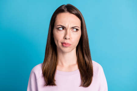 Close-up portrait of nice attractive lovely pretty dissatisfied strict sullen girl looking aside frowning isolated over bright vivid shine vibrant blue color background Imagens