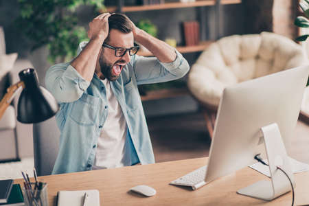 Photo portrait of unhappy man screaming at desktop screen holding head with two hands at table in modern industrial office indoors