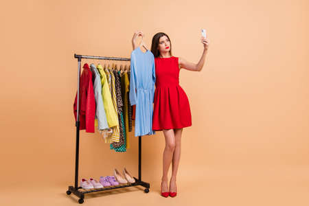Full length photo of doubtful girl take selfie choose dress showroom wear red stilettos dress isolated on beige color background