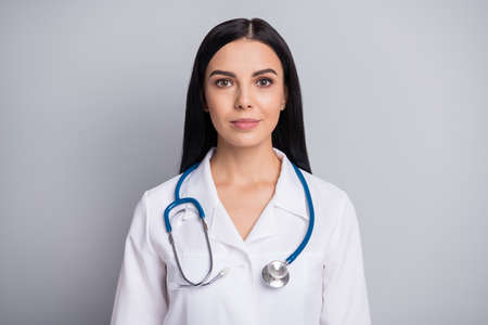 Photo of charming calm young woman look camera wear stethoscope white uniform isolated grey color background