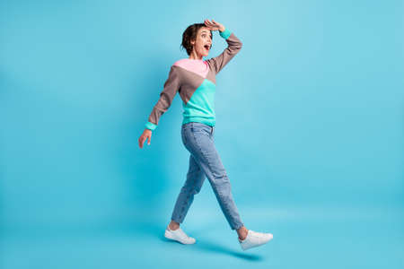 Photo portrait full length of excited woman walking looking into distance with hand near forehead isolated on pastel light blue colored background Banco de Imagens