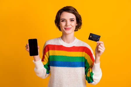 Photo of lovely girl hold debit card phone present screen empty space wear striped sweater isolated yellow color background Stockfoto