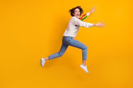 Profile full size photo of optimistic funny girl run hug friend wear rainbow sweater denim jeans white shoes isolated on yellow background Standard-Bild