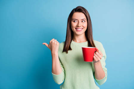 Photo of positive girl point finger empty space hold latte cup wear green sweater isolated over blue color background