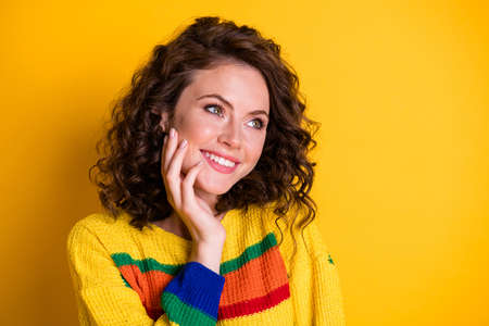 Photo of charming girl palm cheek look empty space imagine wear striped pullover isolated bright yellow color background