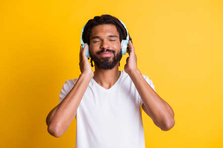 Photo of black guy hold headphones eyes closed smile wear earphones white t-shirt isolated yellow color background Stock fotó