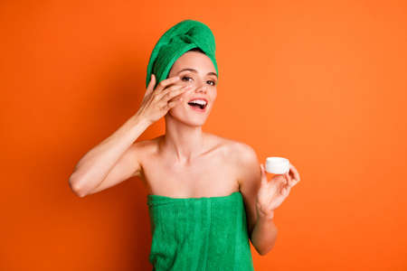 Photo portrait of girl applying cream under eye from jar with finger isolated on bright orange colored background