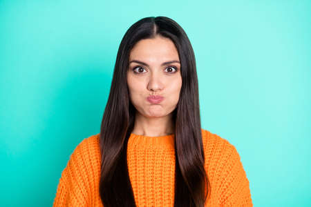 Photo of positive young lady inflate cheeks look camera have fun wear orange sweater isolated teal color background