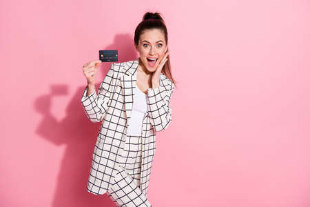 Portrait of impressed lady hold debit card arm on cheek open mouth checkered clothing isolated on pink color background