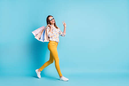 Profile photo of young lady go carry shop bags show v-sign wear sunglass geometry print shirt yellow pants isolated blue color background
