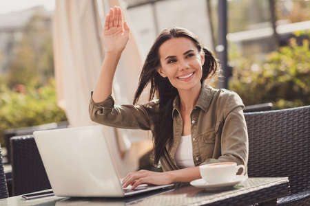Photo portrait of woman working on laptop drinking coffee raising hand asking for receipt in cafe