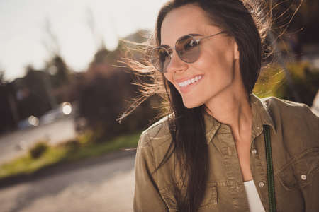 Profile side photo of charming pretty lovely young woman dressed brown shirt eyewear smiling outdoors sunny city