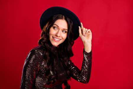 Photo of charming lady look empty space shiny smile wear headwear glossy shirt isolated red color background