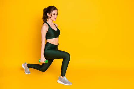 Full length body size view of nice attractive strong focused girl using dumbbells doing sit-ups isolated over bright yellow color background