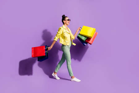 Full body profile side photo of young positive woman go walk shopping sale hold bags wear green pants isolated over purple color background