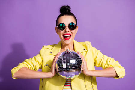 Photo of crazy cool millennial girl hold glitter discotheque ball scream isolated over purple color background
