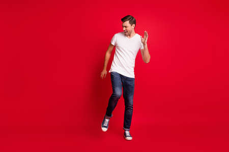 Full size photo of young satisfied man danceng open mouth shout yes isolated on dark red color background