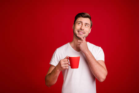 Photo portrait curious dreamy smiling guy keeping beverage on pause looking empty space touching chin isolated bright red color background
