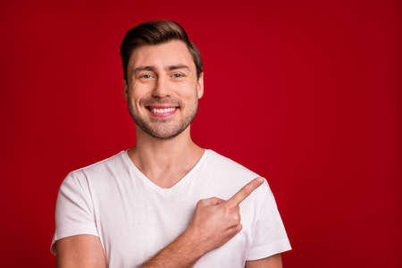 Photo of cheerful young man smile indicate finger empty space isolated on dark red color background
