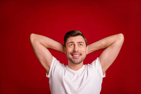 Photo portrait of dreamy male worker relaxing looking up at blank space imagine smiling isolated vivid red color background 版權商用圖片