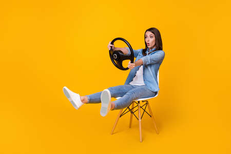 Full length profile photo of pretty funny lady good mood sit chair spread legs hold steering wheel riding imagine car rushing wear casual denim shirt shoes isolated yellow color background