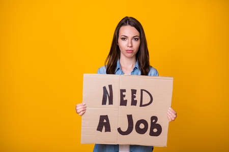 Photo of attractive beautiful young sad business lady bad mood hold carton placard jobless professional seek job work wear casual denim shirt isolated bright yellow color background