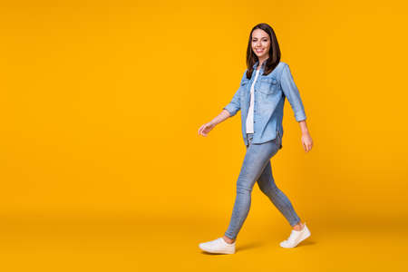Full length profile photo of attractive cheerful lady good mood walking down street nice day weather wear casual denim shirt sneakers isolated vivid yellow color background