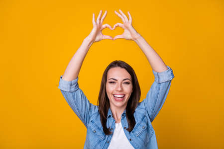 Photo of attractive cheerful lady good mood express romance cardiac feelings showing arms fingers heart shape symbol above head wear casual denim shirt isolated yellow color background