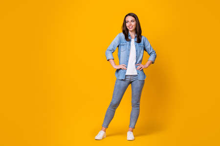 Full length photo of attractive pretty confident lady arms by sides good mood adorable appearance look side empty space wear casual denim shirt shoes isolated vibrant yellow color background 版權商用圖片