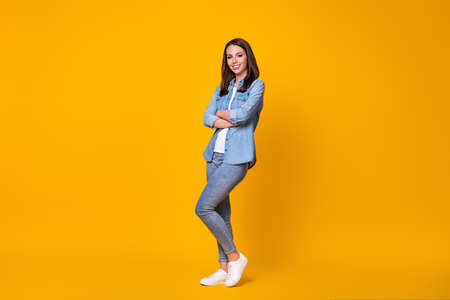 Full size profile photo of attractive confident business lady arms crossed good mood freelancer youngster beaming smile wear casual denim shirt shoes isolated vivid yellow color background 版權商用圖片