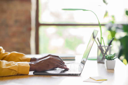 Profile photo of girl hands typing on laptop table wear yellow shirt at home