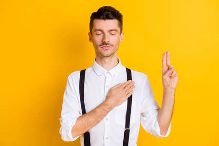 Photo portrait of peaceful calm man swearing hand on heart closed eyes isolated on vibrant yellow color background Banque d'images
