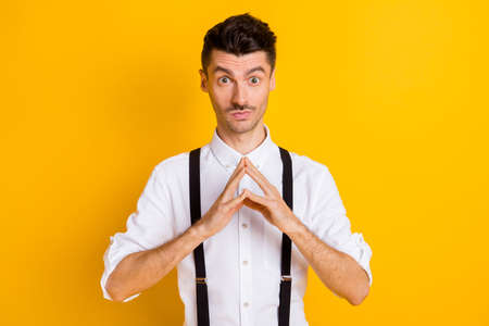 Photo portrait of thoughtful curious man keeping fingers together got idea wearing suspenders isolated on vibrant yellow color background Banque d'images