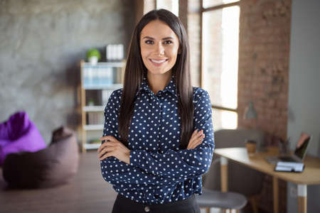Photo of young beautiful attractive cheerful smiling happy confident businesswoman with crossed hands at office workshop