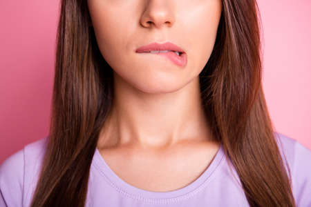 Close-up photo portrait of woman biting lower lip isolated on pastel pink colored background