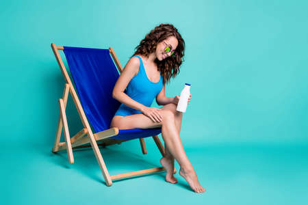 Full length photo girl tourist rest relax travel exotic warm country recreation sit deckchair apply spf sunblock sunscreen bottle sun bathing wear blue swimsuit isolated teal color background