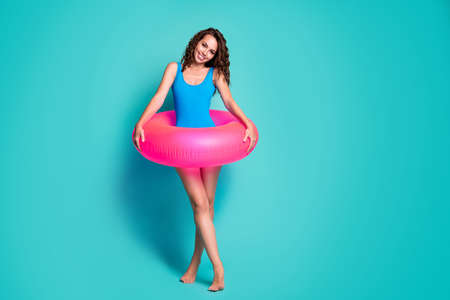 Full length body size view of her she attractive pretty cheerful cheery girl wearing pink safety buoy swimwear enjoying leisure weekend isolated bright vivid shine vibrant blue color background