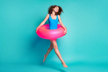 Full length body size view of her she attractive cheerful cheery dreamy glad girl jumping wearing pink safety buoy going having fun isolated bright vivid shine vibrant blue color background