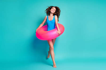 Full length body size view of her she attractive cheerful cheery girl jumping wearing pink safety buoy going having fun plage journey isolated bright vivid shine vibrant blue color background