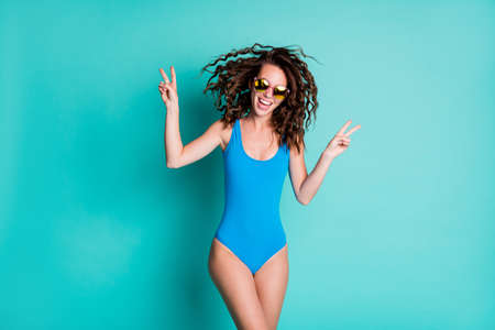 Photo of cheerful active careless young lady model open mouth show v-sign blowing hairstyle slender figure beach seaside chilling wear blue swimsuit isolated turquoise color background