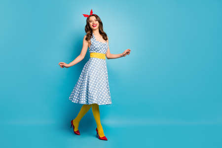 Full length photo of candid lovely tender gentle girl enjoy spring time go walk wear retro style outfit bright headband pantyhose tights stilettos isolated over blue color background